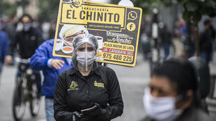 A woman promotes a sandwich restaurant in downtown Lima mandatory national quarantine due to the COVID-19 coronavirus pandemic
