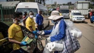 Un trabajador municipal reparte jabón y follestos informativos sobre higiene en el densamente poblado 'township' de Diepsloot, en Johannesburgo, el 21 de marzo de 2020