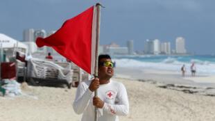 Un salvavidas coloca una bandera roja en la playa para advertir a los bañistas de los peligros debido a la proximidad del huracán Zeta, en Cancún, México, el 26 de octubre de 2020.