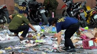 Scattered debris including items traditionally sold for New Year celebrations, such as cardboard and plastic horns and gifts, as well as a bloody slipper, lay at the mall's entrance where the explosion took place