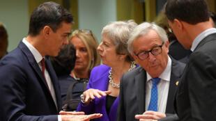 El presidente del gobierno de España, Pedro Sánchez, conversa con la primera ministra Theresa May en una de las pausas de la Reunión de Líderes de la Unión Europea en Bruselas el 18 de octubre de 2018. En primer plano, el presidente de la comisión Europea, Jean-Claude Juncker, conversa con el primer ministro del Reino de los Países Bajos, Mark Rutte.
