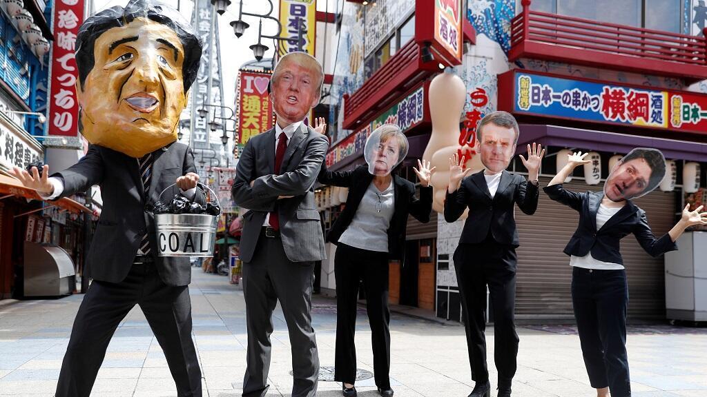 Los manifestantes usan máscaras de los líderes del G20, mientras exigen que Japón deje de apoyar el carbón en su país, durante una manifestación en Osaka, Japón, el 28 de junio de 2019.