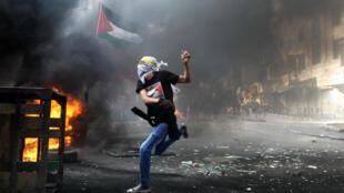 Des Palestiniens défiant des membres des forces de sécurité israéliens à Hébron (Cisjordanie), le 9 octobre 2015.