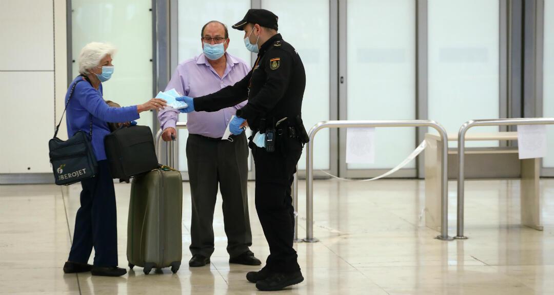 Un oficial de la Policía Nacional entrega mascarillas a dos viajeros que llegan al aeropuerto Adolfo Suárez Barajas. Madrid, España, el 12 de mayo de 2020.