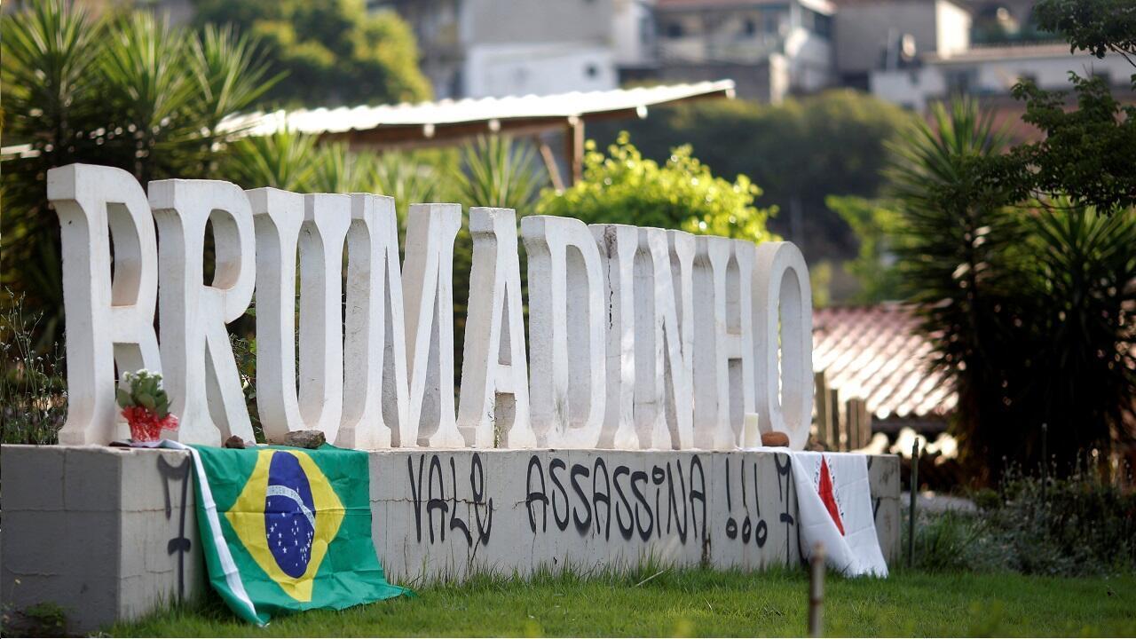"""Un grafiti que dice """"Vale asesina"""", rodeado de la bandera nacional brasileña y la bandera del estado de Minas Gerais, aparece en la entrada de la ciudad de Brumadinho, después de que se derrumbara una represa de la minera brasileña Vale SA."""