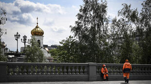 عاملان بلديان يأخذان قسطا من الراحة في وسط موسكو في 14 أيار/مايو 2020.