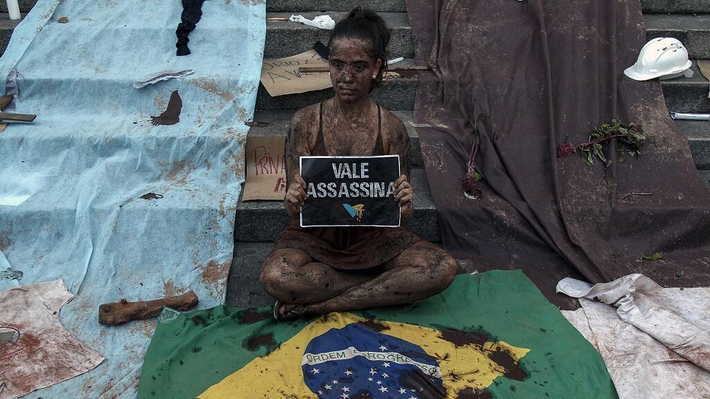 """Una manifestante cubierta de barro, con un cartel que dice """"Vale asesina"""" participa en una manifestación frente a la Catedral de Se en Sao Paulo, Brasil, el primero de febrero de 2019."""