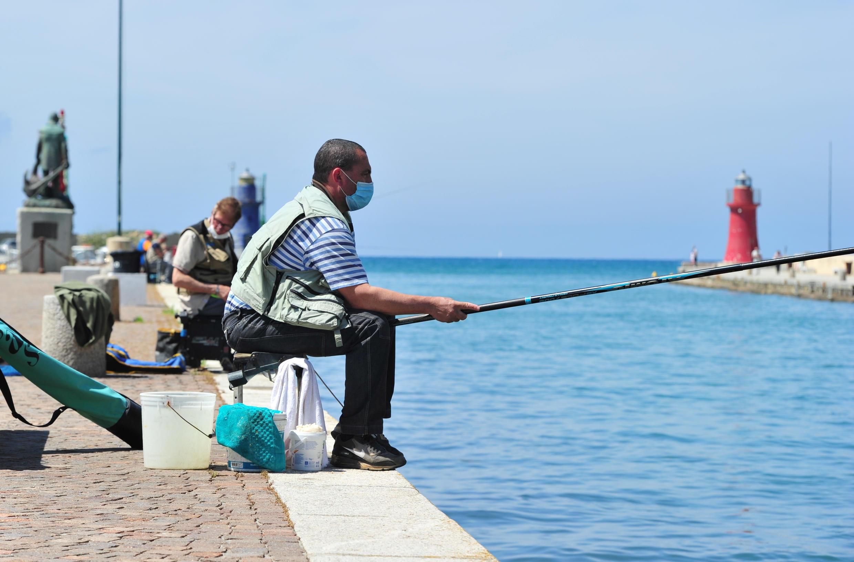 Un pêcheur portant un masque, à Castiglione della Pescaia, en Italie, le 9 mai 2020.
