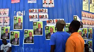 Des Haïtiens regardent les affiches des élections, près le Port-au-Prince, le 5 août 2015.