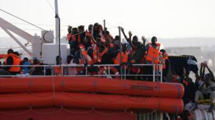 Los migrantes a bordo del barco de la ONG alemana Lifeline, reaccionan con alegría a la llegada al puerto de La Valeta, Malta el 27 de junio, 2018.
