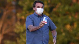 El presidente brasileño Jair Bolsonaro muestra una caja de hidroxicloroquina a sus seguidores fuera del Palacio Alvorada en Brasilia, el 23 de julio de 2020.