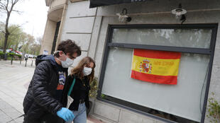 """Marco Donoso del Bufalo, and his sister Irene, walk past a Spanish flag that reads """"Come on, Spain. Together we will succed"""" in Madrid, Spain."""