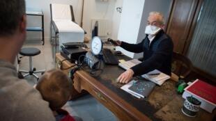Un médecin de Crac'h porte un masque de protection contre le nouveau coronavirus lors de la consultation d'un enfant en présence de son père, à Crac'h, le 4 mars 2020