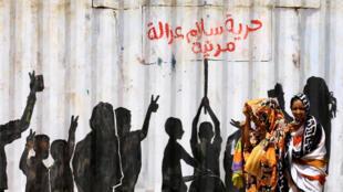 """Civilians walk past graffiti reading in Arabic """"Freedom, Peace, Justice and Civilian"""" in the Burri district of Khartoum, Sudan, July 10, 2019."""