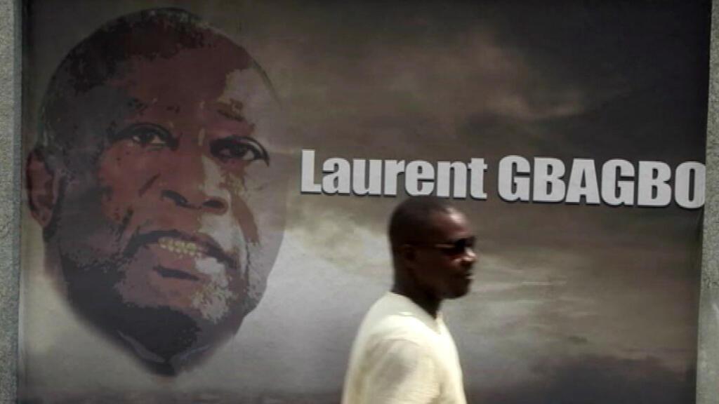 Un passant devant une affiche à l'effigie de l'ancien président Laurent Gbagbo.