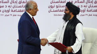 US Special Representative for Afghanistan Reconciliation Zalmay Khalilzad (right) and Taliban co-founder Mullah Abdul Ghani Baradar shake hands after signing a peace agreement in Doh in February 2020