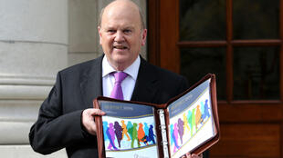 Irish Finance Minister Michael Noonan presents budget documents in Dublin on Tuesday