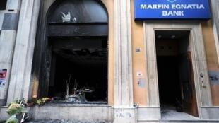 زهور أمام فرع مصرف مارفن بتاريخ 6 أيار/مايو 2010 حيث قتل ثلاثة أشخاص خلال أعمال شغب في أثينا قبل يوم