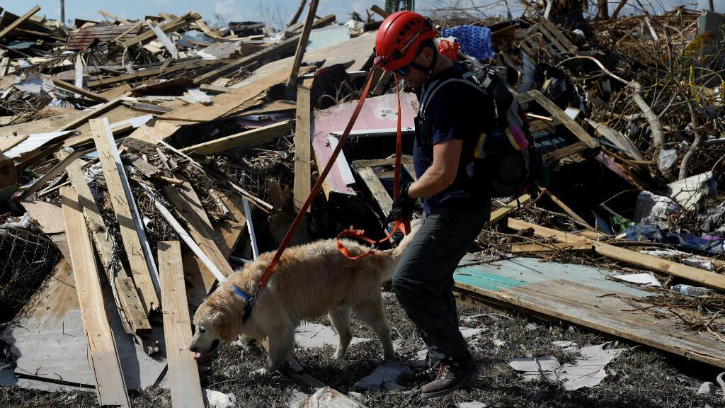 Un miembro de la Fuerza de Tarea de Búsqueda y Rescate de Bomberos Canadienses de Burnaby y un perro buscan a los muertos en el vecindario destruido de Mudd después de que el Huracán Dorian azotara las Islas Ábaco en Marsh Harbour, Bahamas, el 10 de septiembre de 2019.