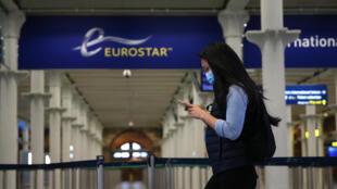 Un passager portant un masque arrive à la gare St Pancras, à Londres, à la sortie de l'eurostar, le 6 mai 2020.