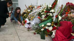Des touristes rendent hommage aux victimes de l'attentat du musée du Bardo, à Tunis, le 27 mars2015.
