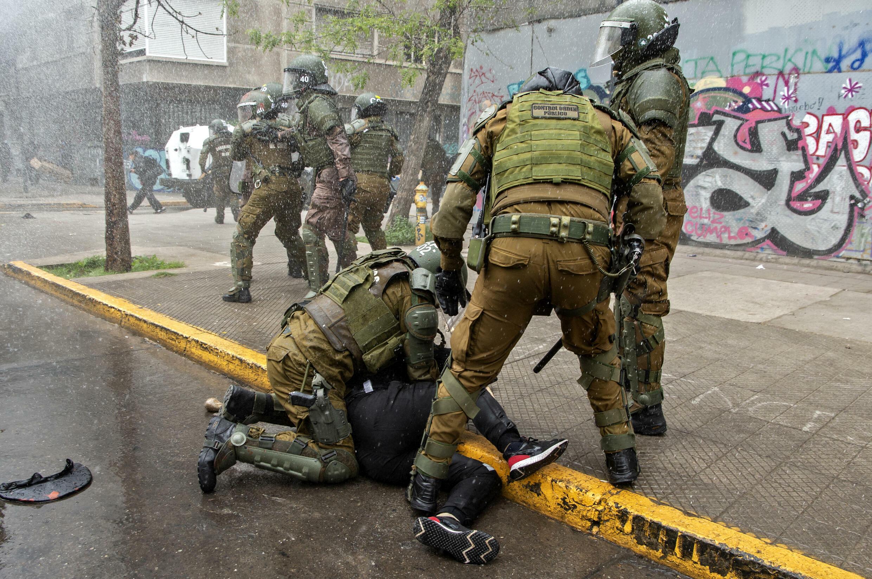 Un manifestante es detenido por policías antidisturbios tras una protesta de indígenas mapuches en el centro de Santiago, el 10 de octubre de 2021, en medio de la conmemoración del Día de la Raza