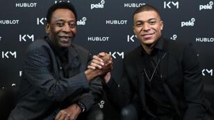 La leyenda del fútbol brasileño Pelé y el delantero del Paris Saint-Germain Kylian Mbappé se dan la mano durante su reunión en el Hotel Lutetia en París el 2 de abril de 2019.