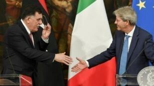 باولو جينتيلوني يصافح فايز السراج أثناء اجتماع لرئيسي حكومتي إيطاليا وليبيا في روما 2017/07/25