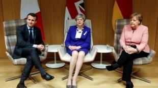 رئيسة وزراء بريطانيا تيريزا ماي بين المستشارة الألمانية انغيلا ميركل والرئيس الفرنسي إيمانويل ماكرون خلال القمة الأوروبية في بروكسل