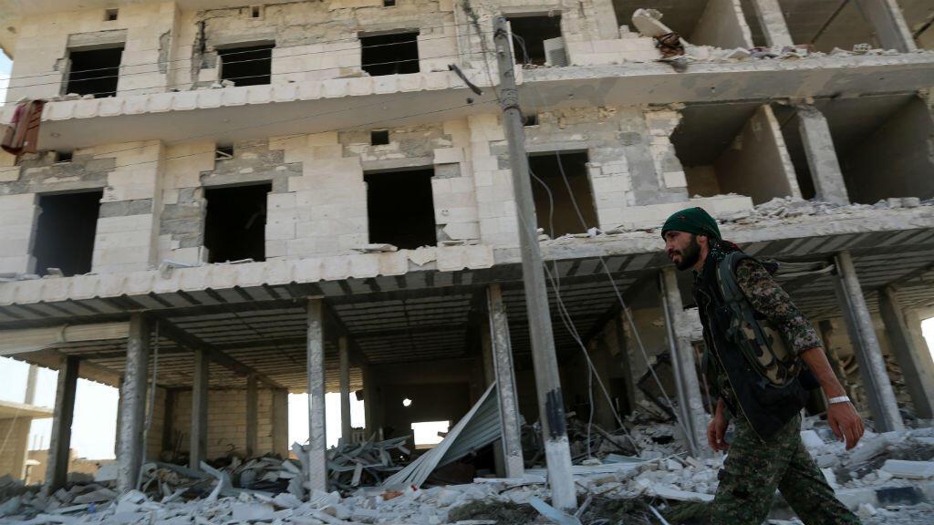 Un membre des forces rebelles syriennes devant un immeuble de Manjib bombardé par la coalition internationale.