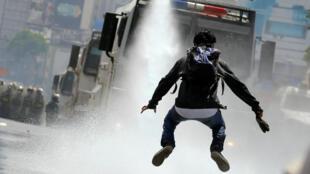 Un manifestante salta para evitar un chorro de agua lanzado desde un vehículo de las fuerzas de seguridad durante una manifestación contra el presidente Nicolás Maduro, en Caracas, Venezuela, el 26 de mayo de 2017.
