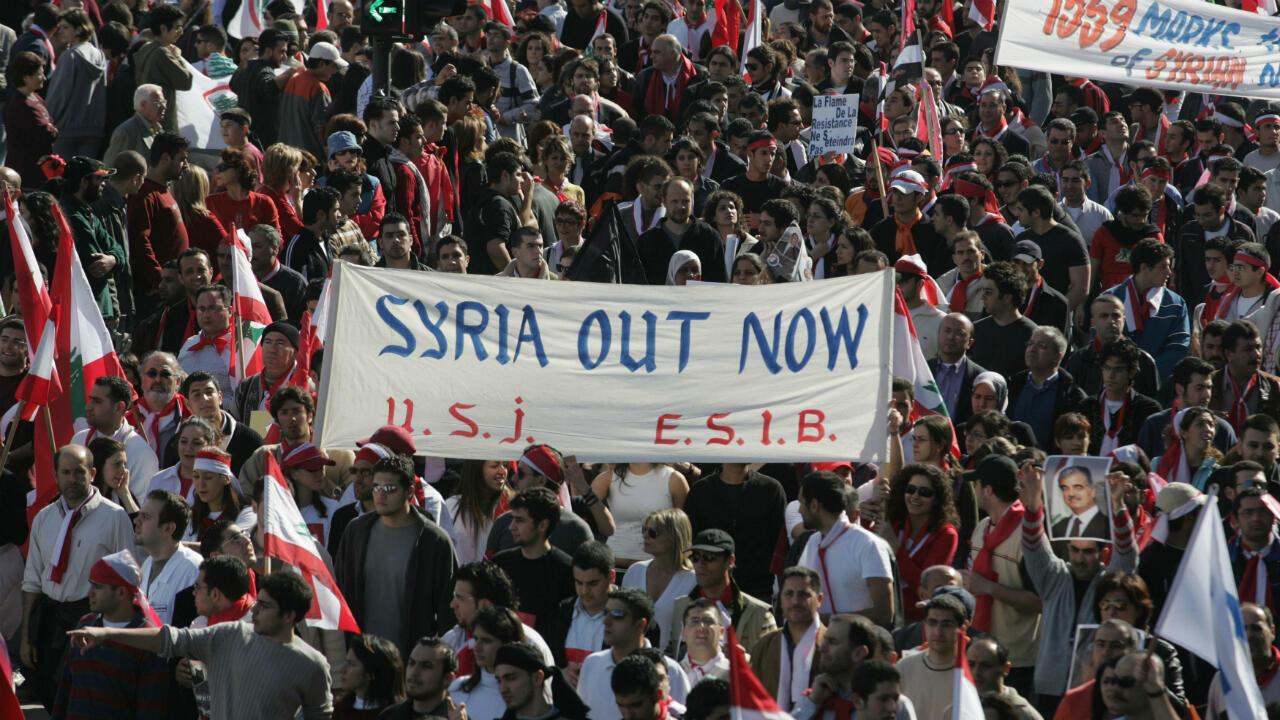 """Imagen de archivo. Manifestantes libaneses sostienen pancartas contrarias a Siria durante una manifestación de la oposición en el centro de Beirut el 21 de febrero de 2005. Decenas de miles de personas se concentraron en el paseo marítimo de Beirut gritando """"Siria Fuera"""" mientras aumentaba la presión sobre el Gobierno y sus partidarios en Damasco una semana después del asesinato. del ex primer ministro Rafik Hariri."""