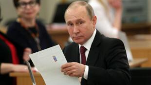 Le président sortant et candidat à sa réélection Vladimir Poutine dans un bureau de vote à Moscou, le 18 mars 2018.
