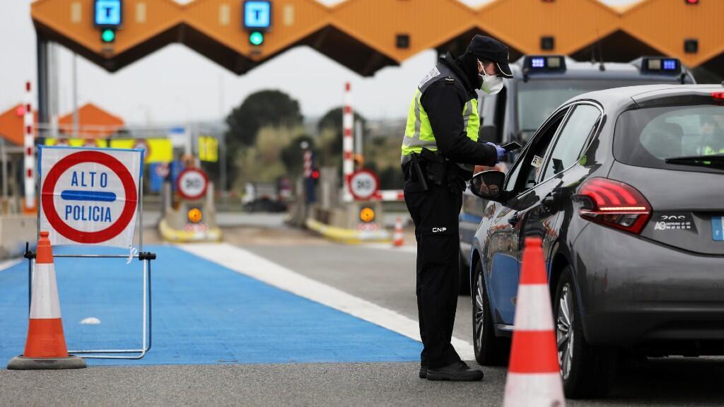 Un policia nacional español para a un vehículo para exigir al conductor el documento de identidad español o la tarjeta de residencia. En la Jonquera, España. 17 de marzo de 2020.
