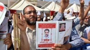 متظاهرون يحملون صورة كمال المطماطي، الذي توفي تحت التعذيب في عهد بن علي، في 29 أيار/مايو في قابس.