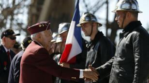 Un vétéran serre la main de pompiers parisiens vêtus d'uniformes d'époque lors d'une célébration du 75e anniversaire de la libération, à Paris le 25 août 2019.