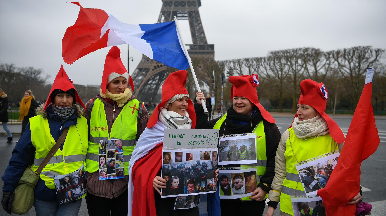 Un grupo de mujeres que hacen parte de la movilización de los chalecos amarillos sostienen fotografías de manifestantes heridos por las fuerzas policiales, en una concentración frente a la Torre Eiffel. París, Francia. 20 de enero de 2019.