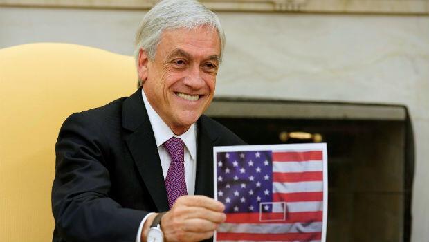 El presidente de Chile, Sebastián Piñera, muestra una imagen de la bandera chilena representada en el centro de la bandera estadounidense durante una reunión con el presidente estadounidense Donald Trump.
