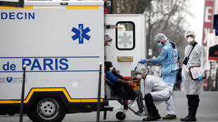 French rescue workers evacuate a patient in Paris on March 20, 2020, as France faces an aggressive progression of the coronavirus disease COVID-19.