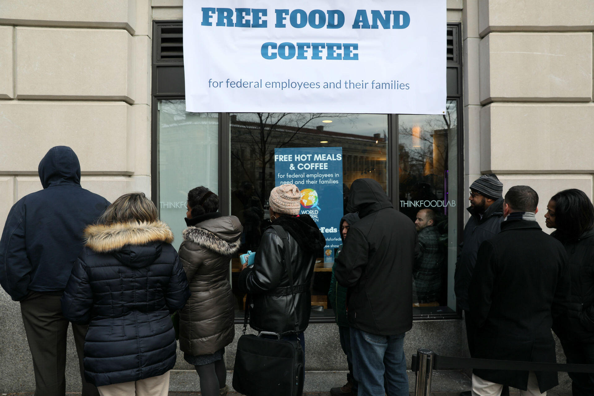 Federal workers left unpaid or furloughed by the extended partial government shutdown stand in line for fresh food and coffee at the World Central Kitchen, a volunteer emergency kitchen run by Chef Jose Andres, in Washington, DC, on January 16, 2019. Hotels, bars and restaurants have stepped in to offer rooms, meals and snacks, free or at a discount, to shutdown-affected workers. Food banks, too, have opened their doors as the stalemate continues.