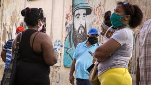 Un grupo de personas hace cola para comprar productos con dólares estadounidenses en una tienda en La Habana, el 20 de julio de 2020. Cuba eliminó el impuesto al dólar y permitió su uso vía tarjeta bancaria para adquirir algunos alimentos y productos de aseo e impulsar su economía, golpeada por la pandemia del nuevo coronavirus y el endurecimiento del bloqueo de EEUU.