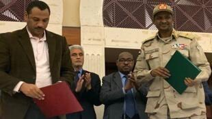 نائب رئيس المجلس العسكري الحاكم السوداني محمد حمدان دجالو (يمينا) وزعيم حركة التحالف من أجل الحرية والتغيير أحمد الربيعة بعد توقيع الاتفاق، الخرطوم- 17 يوليو/تموز 2017