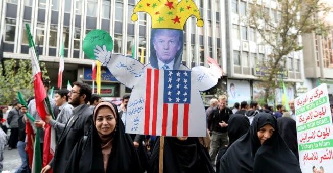 متظاهرون يرفعون صورة دونالد ترامب بسخرية.