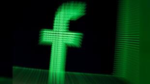 Imagen de archivo. Ilustración de un logotipo de la compañía Facebook con dígitos binarios. 18 de marzo de 2018.