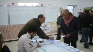 ناخب يتلقى بطاقة في مركز اقتراع أثناء الانتخابات الرئاسية في الجزائر العاصمة، الجزائر في 12 ديسمبر 2019.
