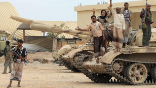 Anti-Houthi militants stand on a tank in southern Yemen on March 24, 2015