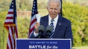 El candidato demócrata a la Presidencia de Estados Unidos, Joe Biden, sostiene su mascarilla mientras habla en un evento de campaña en Gettysburg, Pensilvania, el 6 de octubre de 2020.