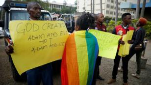 Un activista LGBTI pasa por delante de manifestantes en contra de los derechos de los homosexuales con pancartas fuera del Tribunal Superior de Milimani en Nairobi, Kenia. 24 de mayo de 2019.