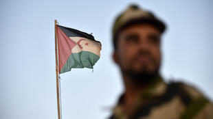 (FILES) In this file photo uniformed soldiers of the pro-independence Polisario Front of the disputed Western Sahara stand before a Sahrawi flag flying at the Boujdour refugee camp near the town of Tindouf in Western Algeria; the territory's ceasefire has been broken