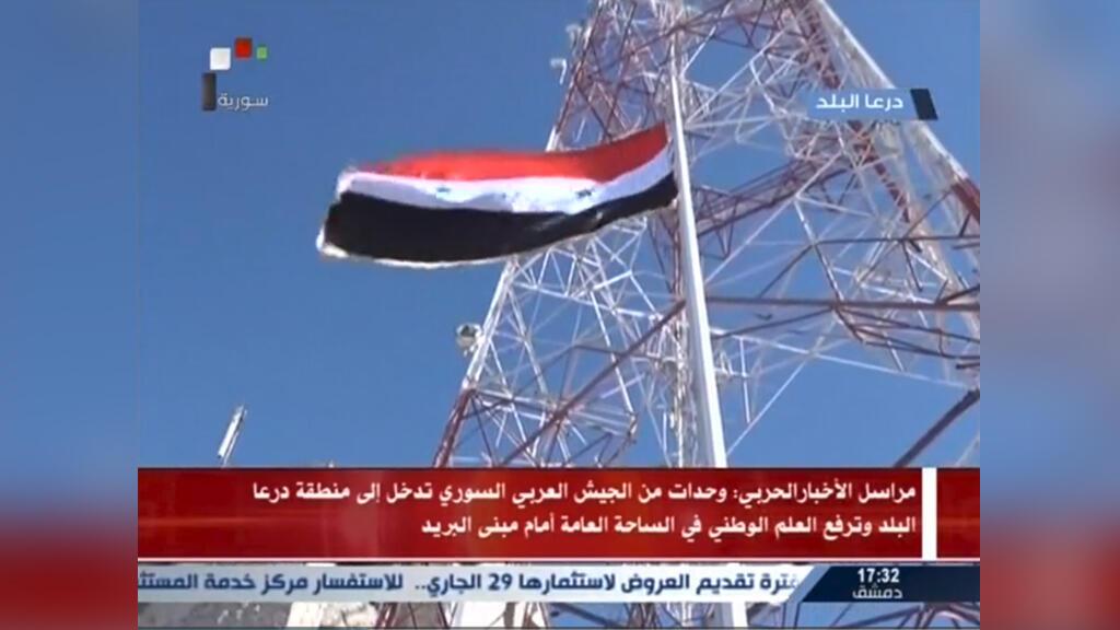 El ejército sirio izando la bandera cerca de la oficina de correos, el único edificio gubernamental que estuvo en manos de los rebeldes.